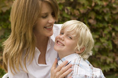 Happy mother hugging her son outside. Royalty Free Stock Images