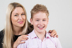 Happy mother hugging smiling son. With disheveled hair in the studio royalty free stock photos