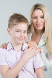 Happy mother hugging smiling son in pink shirt. With disheveled hair in the studio royalty free stock photography