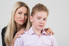 Happy mother hugging a son with disheveled hair. In the studio stock photography