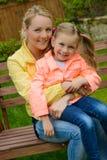 Happy mother hugs her daughter outdoor Stock Photos
