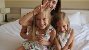 A happy mother hugs two twin daughters in the morning on the bed.