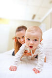 Happy mother and interested baby playing on divan Royalty Free Stock Images