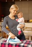 Happy mother ironing while holding baby stock images