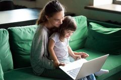 Happy mother with kid daughter having fun online with laptop Stock Photos