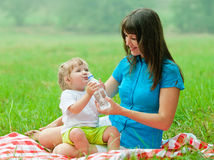 Happy mother and kid drinking water from bottle Stock Image