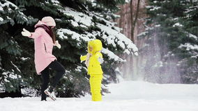 Happy mother and kid enjoy winter snowy day and playing snowballs stock video