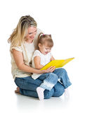 Happy mother and kid girl reading book together Stock Image