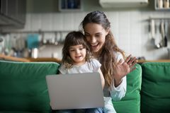 Happy mother and kid girl waving hands making video call Stock Photos
