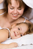 Happy mother and kid lazying. Happy mother and little girl lazying under the blanket - focus on child face Royalty Free Stock Image