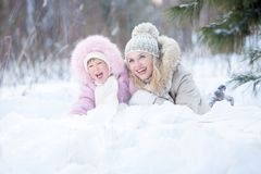 Happy mother and kid lying in snow outdoor Royalty Free Stock Photo