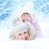 Happy mother and kid lying in snowdrift outdoor Stock Photo