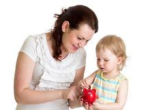 Happy mother and kid put coins into daughter piggy bank Stock Images