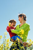 Happy mother with kid on rapeseed field Stock Photo