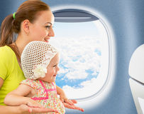 Happy mother and kid sitting near airplane window Stock Image
