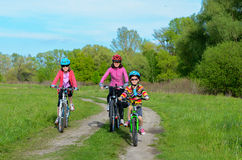 Happy mother and kids on bikes cycling outdoors Stock Images
