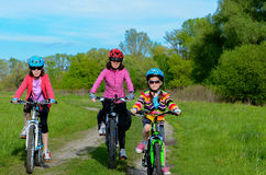 Happy mother and kids on bikes cycling outdoors Stock Photo