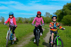 Happy mother and kids on bikes cycling outdoors Royalty Free Stock Photos