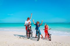 Happy mother with kids biking at beach. Happy mother with kids biking at tropical beach royalty free stock photography