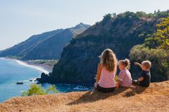 Happy mother, kids on hill with sea cliffs scenic view royalty free stock image