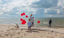 Happy mother and kids with red balloons at sea Royalty Free Stock Images