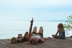 Happy mother, kids relaxing, talking on veranda with beautiful view stock images