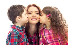 Happy mother kissed by her daughter and son. Portrait of children kissing her mother with flowers. Mothers day concept. Family holiday. Isolated white background royalty free stock photos