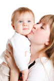 Happy mother kisses baby. Happy mother kisses her cute baby son Stock Image