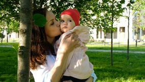 Happy mother kisses her baby on the cheek and plays with a leaf in the city park at sunset.  Royalty Free Stock Photography