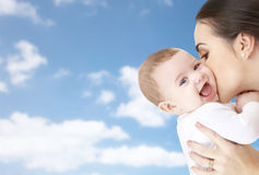 Happy mother kissing adorable baby. Family, motherhood, parenting, people and child care concept - happy mother kissing adorable baby over blue sky background Stock Images