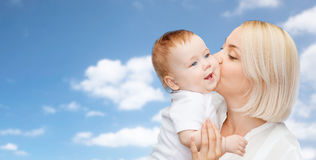Happy mother kissing adorable baby. Family, motherhood, parenting, people and child care concept - happy mother kissing adorable baby over blue sky background Stock Photo
