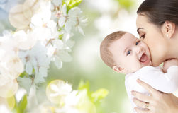 Happy mother kissing adorable baby. Family, motherhood, parenting, people and child care concept - happy mother kissing adorable baby over green natural Stock Images