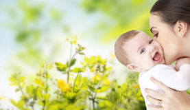 Happy mother kissing adorable baby. Family, motherhood, parenting, people and child care concept - happy mother kissing adorable baby over green natural Stock Image
