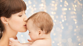 Happy mother kissing adorable baby. Family, motherhood, parenting, people and child care concept - happy mother kissing adorable baby over holidays lights Royalty Free Stock Photo