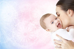 Happy mother kissing adorable baby. Family, motherhood, parenting, people and child care concept - happy mother kissing adorable baby over rose quartz and Royalty Free Stock Image