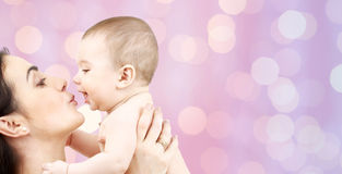 Happy mother kissing adorable baby Stock Images