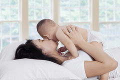 Happy mother kissing baby on bed Stock Photos