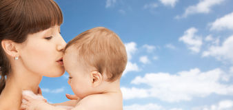 Happy mother kissing baby boy over sky background. Family, children and people concept - happy mother kissing baby boy over blue sky and clouds background Royalty Free Stock Image