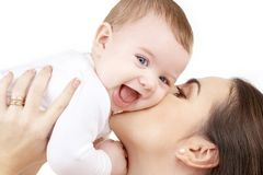 Happy mother kissing baby. Family, child and parenthood concept - happy mother kissing smiling baby