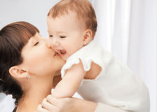 Happy mother kissing baby Stock Photos