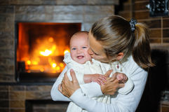 Happy mother kissing baby girl by the fireplace Royalty Free Stock Image