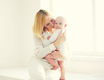 Happy mother kissing baby at home in white room Stock Photo