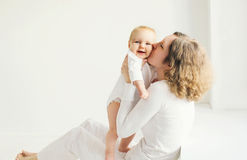 Happy mother kissing baby at home in white room Stock Image