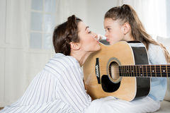 Happy mother kissing cute little daughter with guitar Royalty Free Stock Images