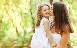 Happy mother kissing daughter walking on the park