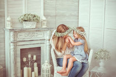 A happy mother is kissing the hand of her daughter. ? happy mother is kissing the hand of her young daughter. They are sitting in the armchair.They are having Royalty Free Stock Photo