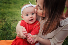 Happy mother kissing her baby daughter on the walk Royalty Free Stock Photos