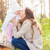 Happy mother kissing her baby at outdoor, autumn park Stock Image