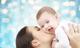 Happy mother kissing her baby over blue lights. Family, motherhood, children, parenthood and people concept - happy mother kissing her baby over blue holidays Royalty Free Stock Photos