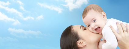 Happy mother kissing her baby over blue sky. Family, motherhood, children, parenthood and people concept - happy mother kissing her baby over blue sky and clouds Stock Image
